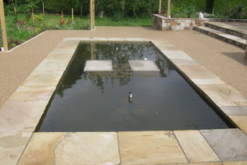Water feature, paving, resin bound gravel and raised beds.