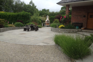 Grey sandstone paving with Irish limestone raised beds.