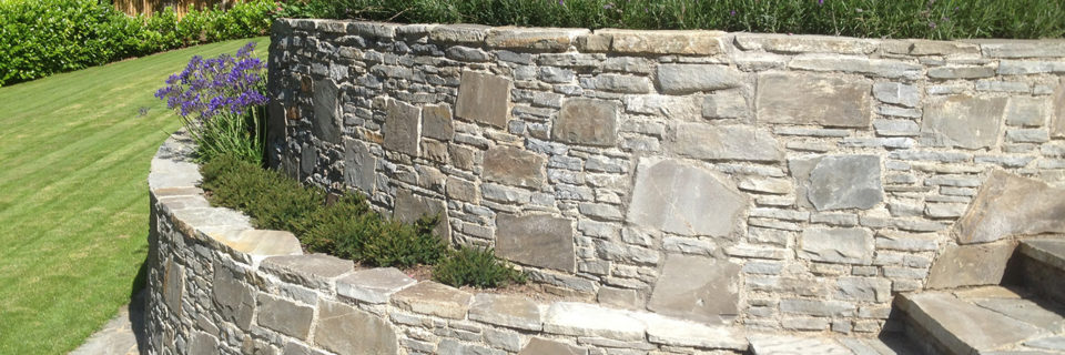 Features stone steps integrated to match retaining walls.